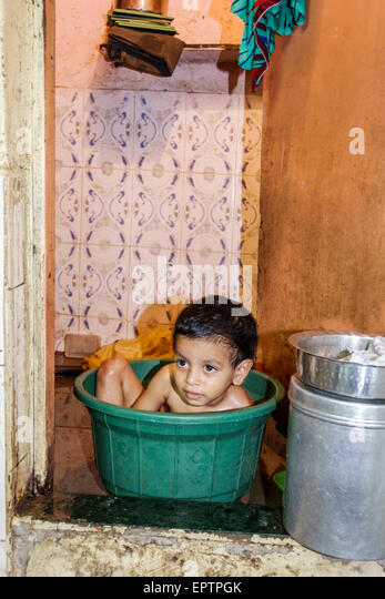 India Asian Mumbai Dharavi Kumbhar Wada slum high population density poverty low income poor resident girl bathing - Stock Image