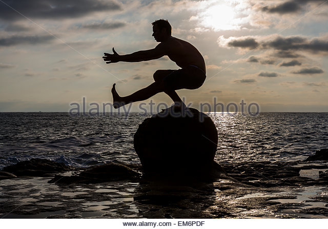 The silhouette of a shirtless male CrossFit athlete as he performs a pistol or one-legged squat on a rock in the - Stock-Bilder