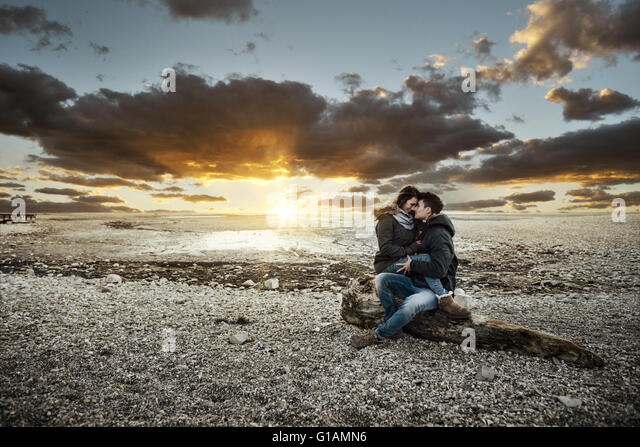 Young couple having a romantic date at the lake, they are hugging and sitting on a trunk on the beach, love and - Stock-Bilder