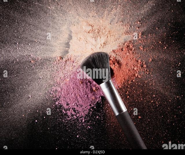 Makeup brush over multicolor blush splatter - Stock Image