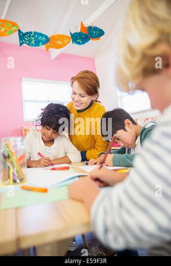 Students and teacher drawing in classroom - Stock-Bilder