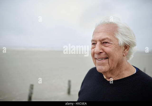 Smiling senior man looking away on beach - Stock Image