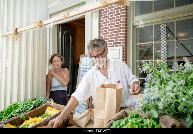Farmer selling organic food on stall outside store - Stock Image