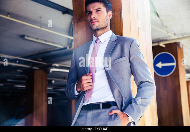 Portrait of a pensive businessman standing in underground parking - Stock Image