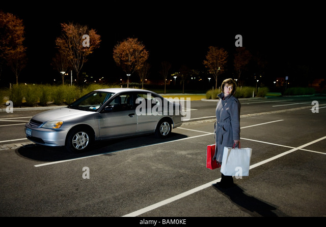 Woman alone in car park - Stock Image