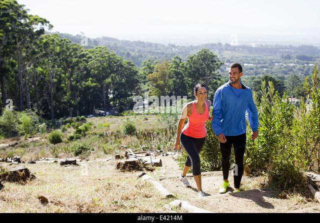Young joggers walking in forest - Stock Image