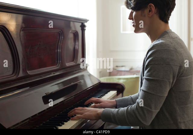 Young man playing piano - Stock-Bilder