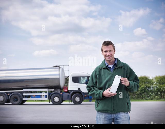 Trucker holding goat's milk by tanker - Stock Image