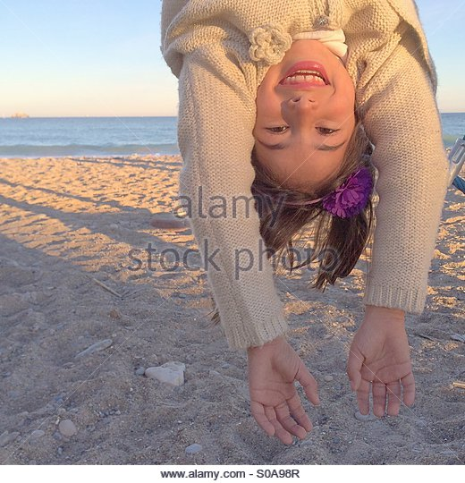 6 years old girl hanging upside down at the beach having fun - Stock Image