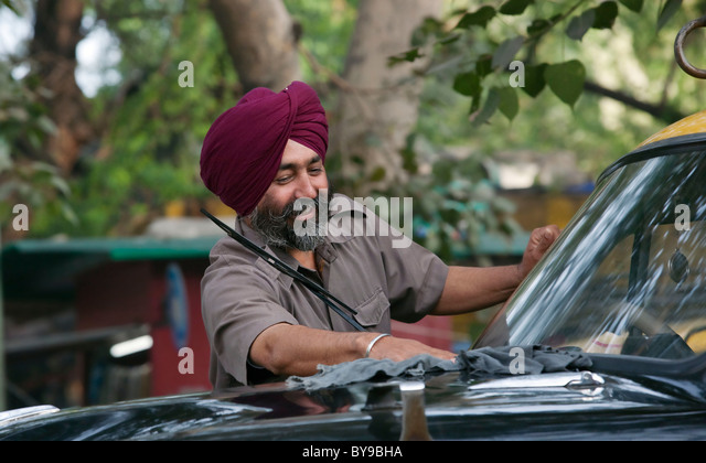 Sikh taxi driver cleaning his vehicle - Stock Image