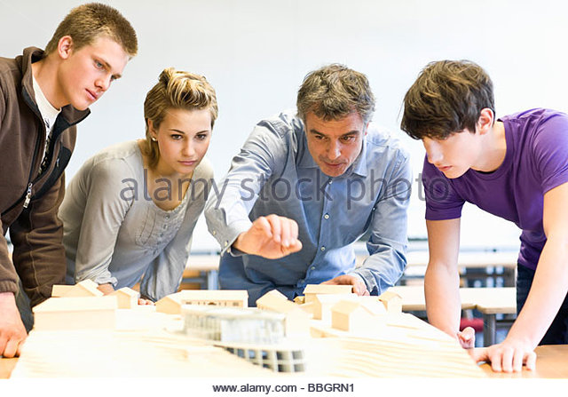 Mature man and teens gathered around an architectural model - Stock-Bilder