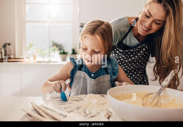 Shot of little girl adding flour to the batter in bowl. Mother teaching her daughter to cook in kitchen at home. - Stock Image