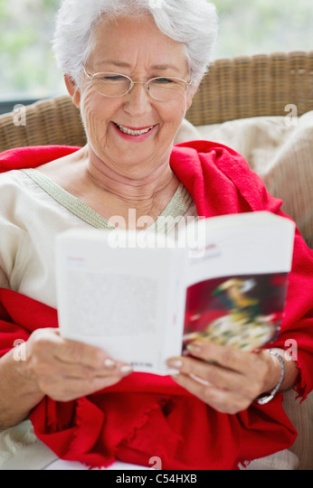 Senior woman reading a magazine and smiling - Stock Image