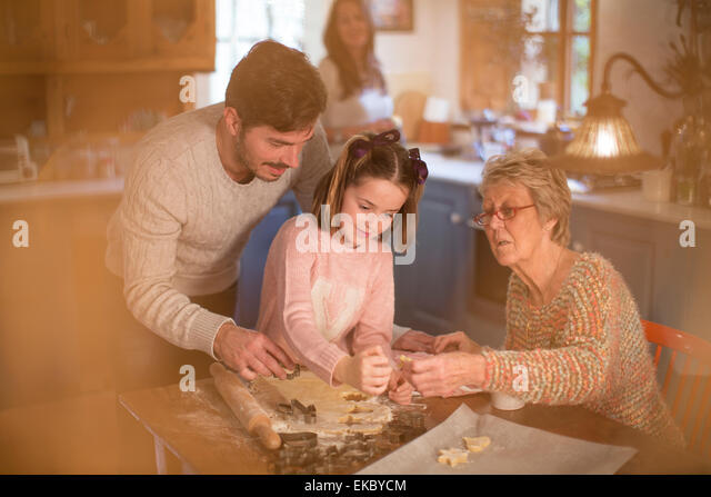 Three generation family cutting shapes in dough to make homemade cookies - Stock Image