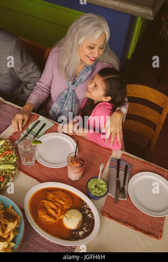 High angle view of grandmother hugging granddaughter in restaurant - Stock Image