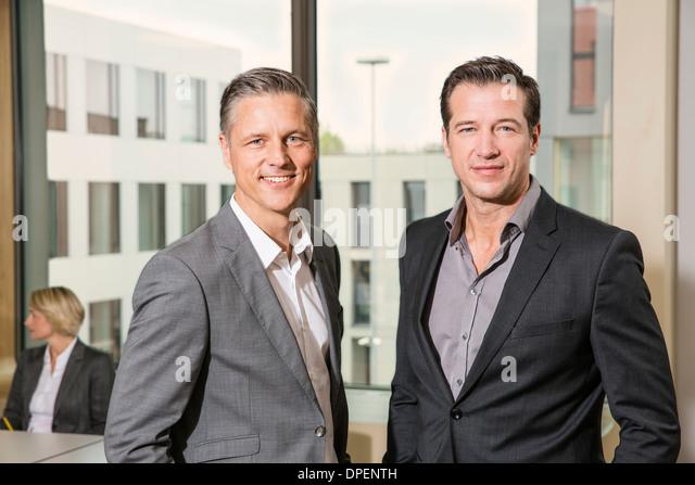 Businessmen standing in conference room - Stock-Bilder