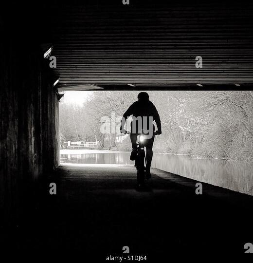 Cyclist on a canal towpath near Leeds. - Stock Image