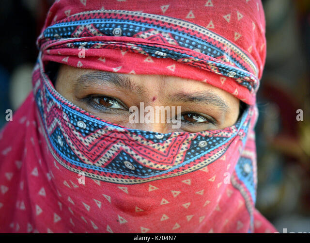 Mature Indian woman with beautiful eyes, covering her hair and face with a trendy secular, red headscarf; Junagadh, - Stock Image