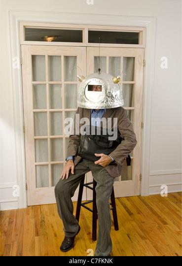 man looking away wearing helmet with antennas - Stock Image