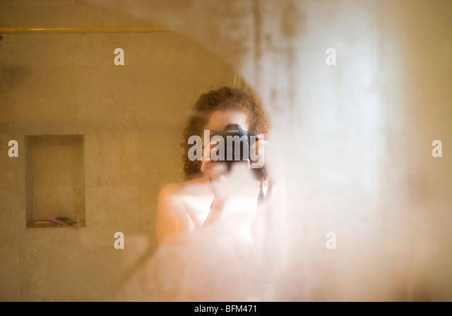 photographer self portrait reflection in the bathroom mirror - Stock Image