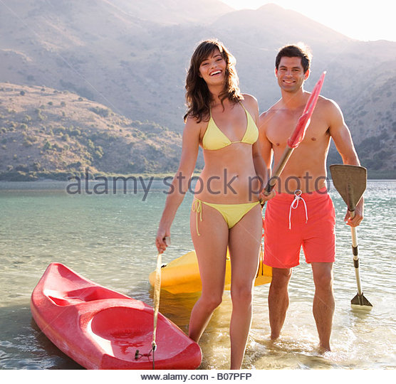 A couple canoeing on a lake - Stock Image