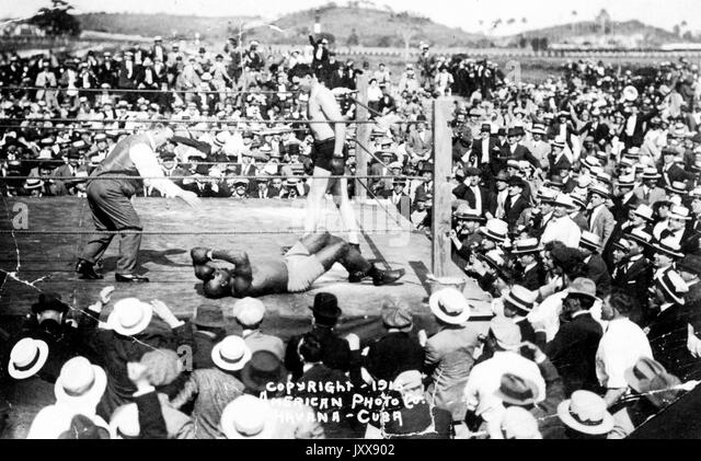 A large group of spectators stands around an outdoor boxing ring, in which are Jack Johnson (right), a referee (left), - Stock Image