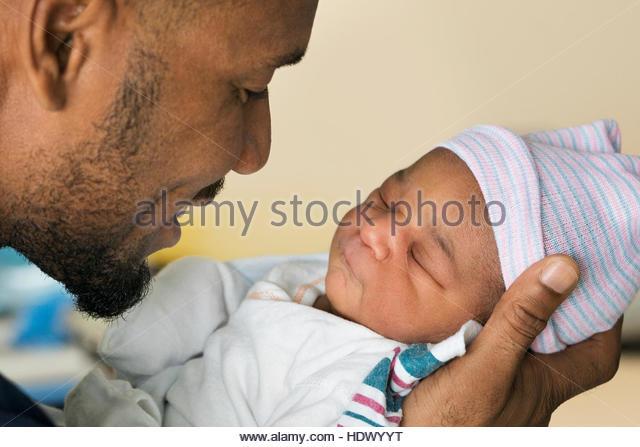 Black father cradling newborn son - Stock Image
