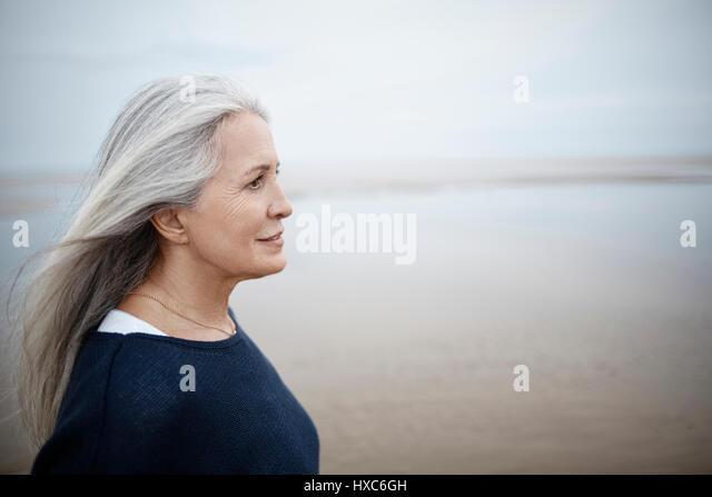 Pensive senior woman looking away on winter beach - Stock Image