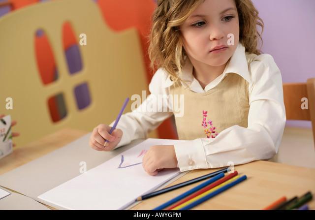 Girl drawing, looking sideward - Stock Image