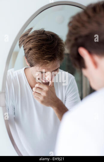 Man laughing to self, reflection in mirror - Stock Image