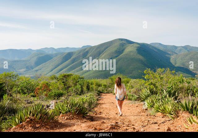 Woman walking along dirt pathway, rear view, Hierve el Agua, Oaxaca, Mexico. - Stock-Bilder