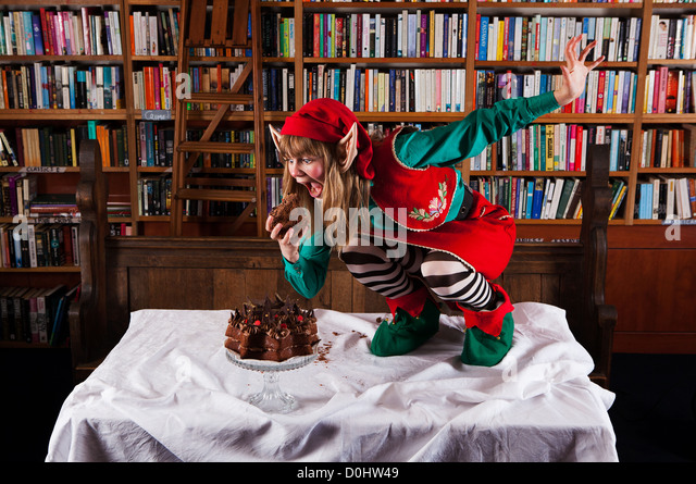 Elf character dressed in red and green Christmas outfit eating a chocolate cake in a bookshop or library. - Stock Image