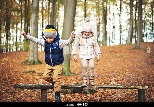 Jumping kids from the bench in forest. Horizontal outdoors shot - Stock Image