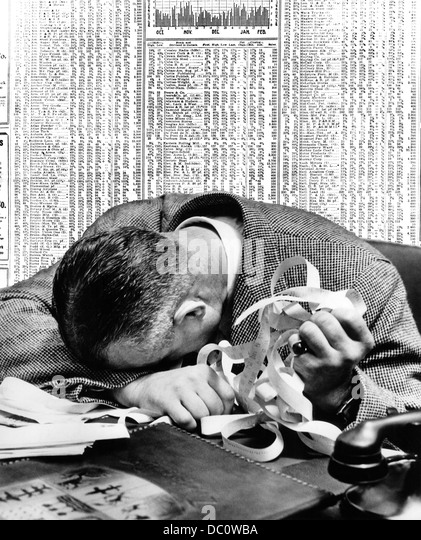 1940s MAN HEAD ON DESK HOLDING STOCK TICKER TAPE WITH NEWSPAPER STOCK PAGE BEHIND HIM - Stock Image