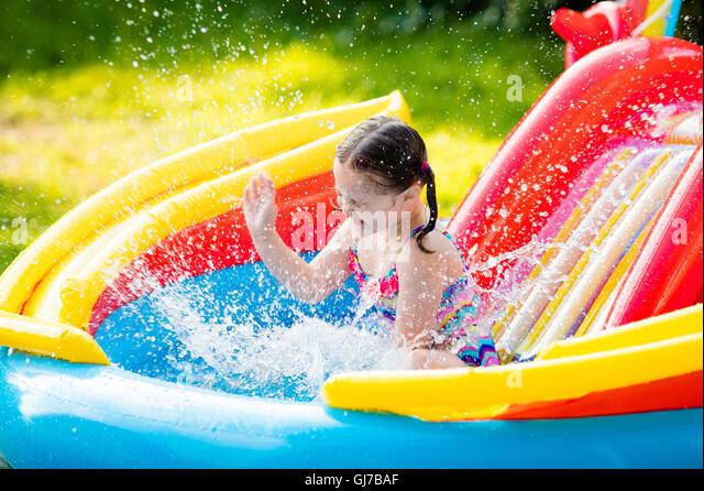 Kids playing in backyard swimming stock photos kids for Baby garden pool