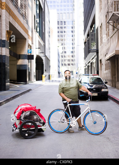 Man with Bicycle and Trailer - Stock Image