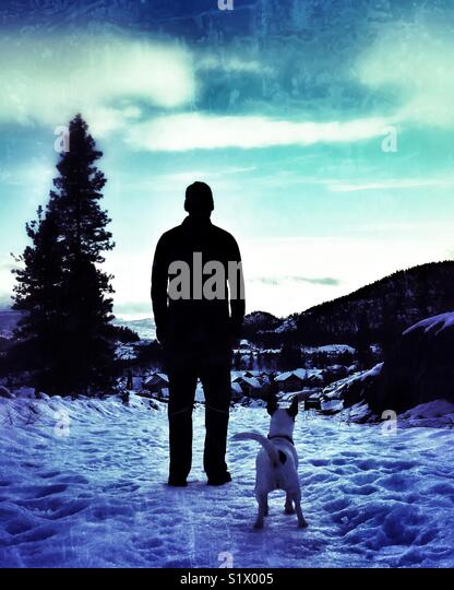 Silhouette of a man standing in the snow with his dog. - Stock Image