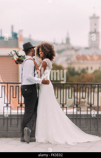 Lovely african newlyweds softly holding each other and smilling. Rooftop. Ancient Lviv architecture on background - Stock-Bilder