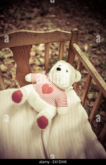 A teddy bear left behind in a vintage baby crib. - Stock Image