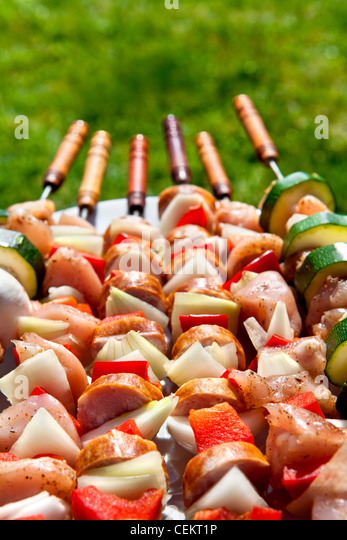 few raw shashliks with green grass in the background - Stock Image