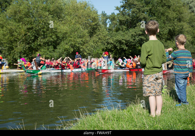 Two young boys cheer on the dragon boats - Stock Image