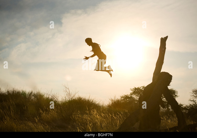 Bushmen tribal man jumping off fallen tree, Kalahari Desert, Namibia - Stock Image