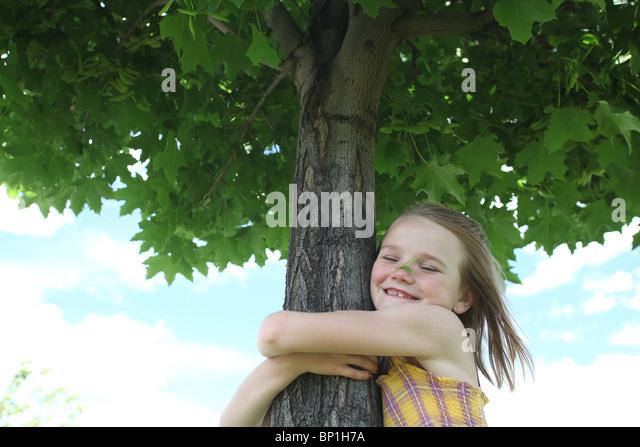 girl hugging maple tree - Stock Image