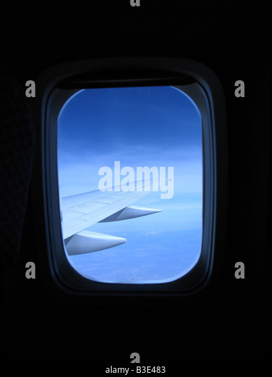 Looking out an airplane's cabin window with a view of the wing and blue sky - Stock Image