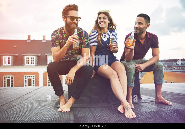 Happy group of three barefoot adults drinking beer on roof outdoors with copy space in sky - Stock Image