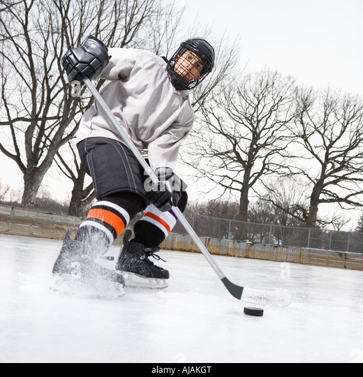 Boy in ice hockey uniform skating on ice rink moving puck - Stock Image