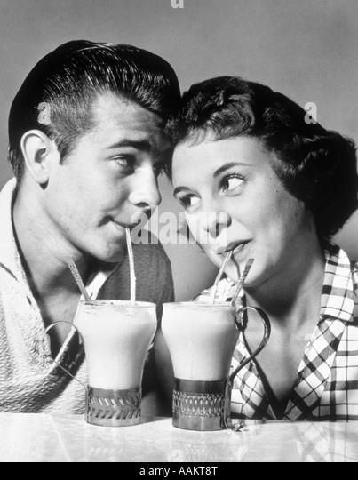 1940s 1950s ROMANTIC TEENAGE COUPLE BOY AND GIRL HEAD TO HEAD DRINKING ICE CREAM SODAS - Stock-Bilder