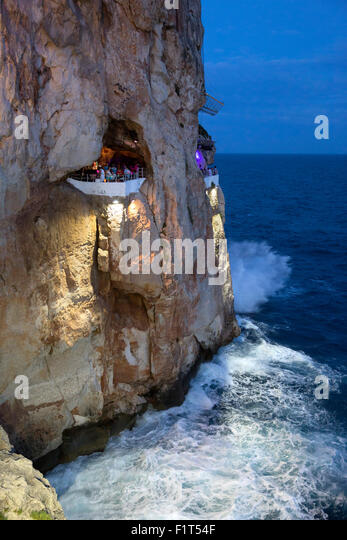 Bar built in cliff caves, Cova d'en Xoroi in evening, Cala en Porter, Menorca, Balearic Islands, Spain, Mediterranean, - Stock Image