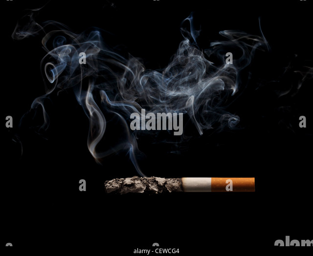 Burning and smoking cigarette on a black background stock image