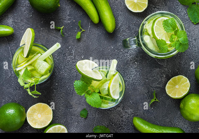 Refreshing drinks with cucumber, lime, mint on dark background. Detox concept. Top view - Stock Image